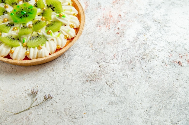 Vista frontal deliciosa sobremesa de kiwi com creme branco e kiwis fatiados em piso branco sobremesa bolo creme fruta tropical