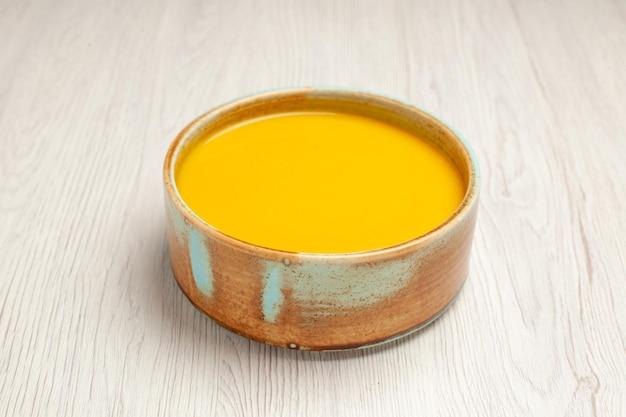 Vista frontal deliciosa sopa de creme sopa de cor amarela na mesa branca molho de sopa refeição prato de creme jantar