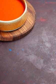 Vista frontal deliciosa sopa de tomate cozida com tomates vermelhos frescos no espaço escuro