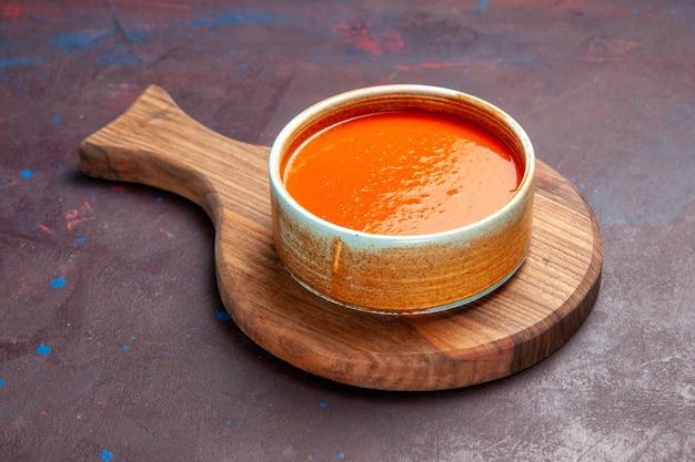 Vista frontal deliciosa sopa de tomate cozida com tomates vermelhos frescos no espaço escuro Foto gratuita