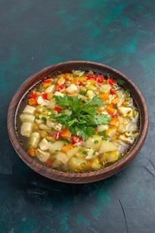 Vista frontal deliciosa sopa de vegetais com diferentes ingredientes dentro de um prato marrom na mesa escura