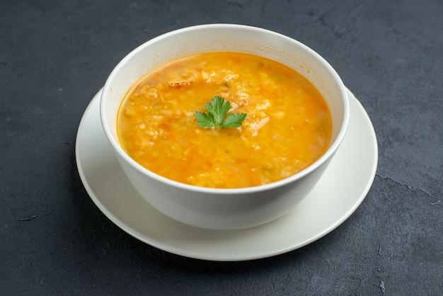 Vista frontal deliciosa sopa dentro de um prato branco em uma superfície escura