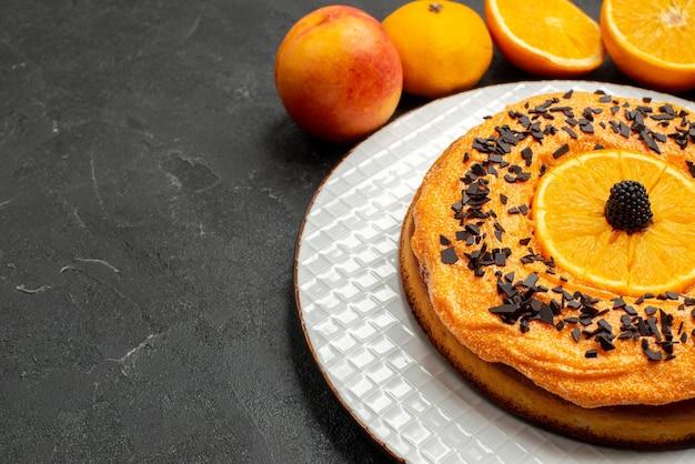 Vista frontal deliciosa torta com fatias de laranja em fundo escuro frutas sobremesa torta bolo biscoito chá