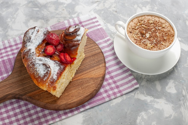 Vista frontal deliciosa torta de morango assada e saborosa fatia de sobremesa com uma xícara de café na mesa branca