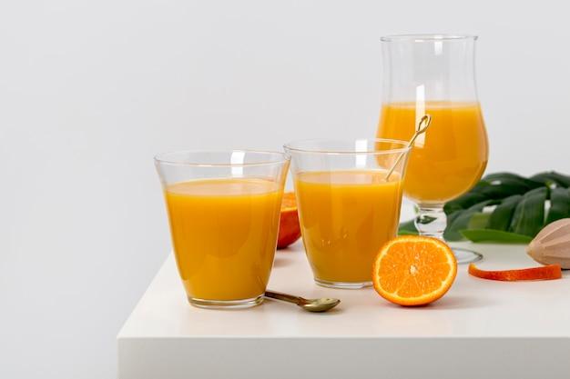 Vista frontal deliciosa variedade de batidos de laranja