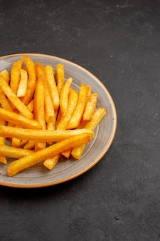 Vista frontal deliciosas batatas fritas dentro do prato no espaço escuro