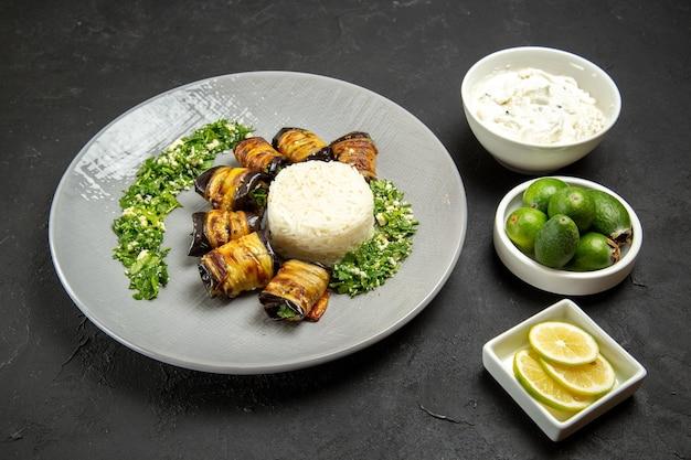 Vista frontal deliciosas berinjelas cozidas com arroz, limão e feijoa na superfície escura jantar comida óleo de cozinha farinha de arroz
