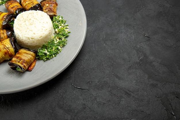 Vista frontal deliciosas berinjelas cozidas com verduras e arroz na mesa escura jantar comida óleo de cozinha farinha de arroz