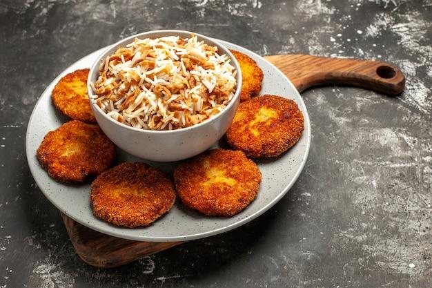 Vista frontal deliciosas costeletas fritas com arroz cozido em um prato de rissol de carne de superfície escura