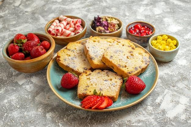 Vista frontal deliciosas fatias de bolo com frutas em uma torta doce de superfície leve bolo de frutas