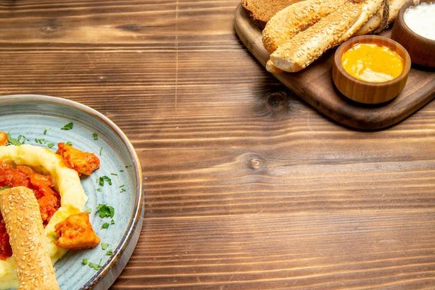 Vista frontal deliciosas fatias de frango com purê de batata e pão na mesa de madeira refeição de batata comida pimenta picante
