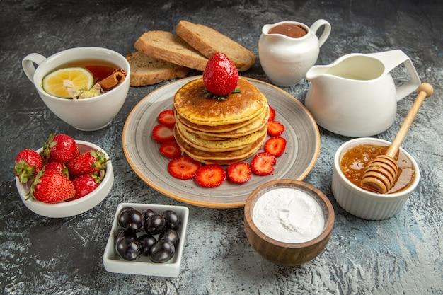 Vista frontal deliciosas panquecas com chá e frutas na superfície clara bolo de frutas doce