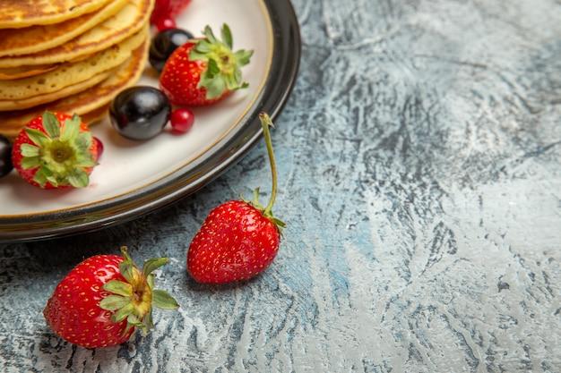 Vista frontal deliciosas panquecas com frutas e bagas na superfície clara bolo de frutas doce