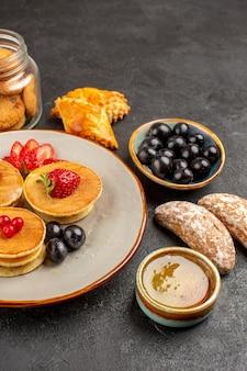 Vista frontal deliciosas panquecas com frutas e bolos em um bolo de frutas doces de superfície escura
