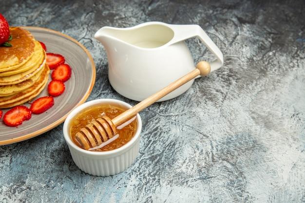 Vista frontal deliciosas panquecas com frutas e mel em bolo de frutas de superfície clara