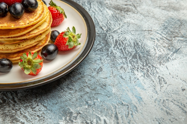 Vista frontal deliciosas panquecas com frutas e morangos em bolo de superfície escura sobremesa de frutas