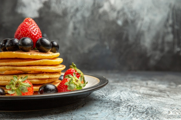 Vista frontal deliciosas panquecas com frutas e morangos na superfície escura bolo de frutas sobremesa