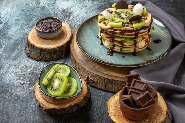 Vista frontal deliciosas panquecas com frutas fatiadas e chocolate