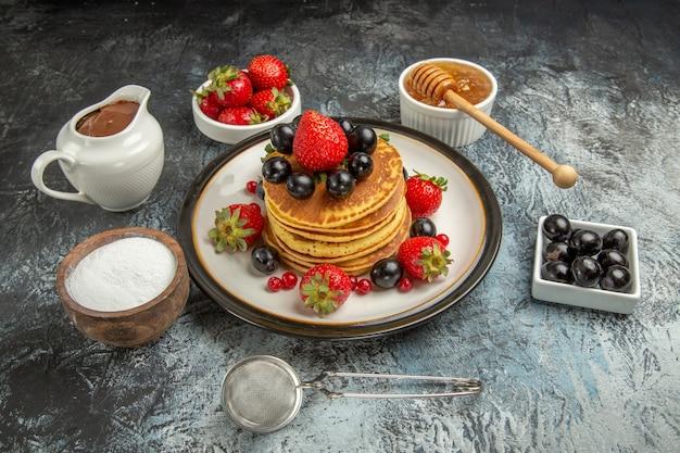 Vista frontal deliciosas panquecas com frutas frescas em um bolo de frutas de superfície clara