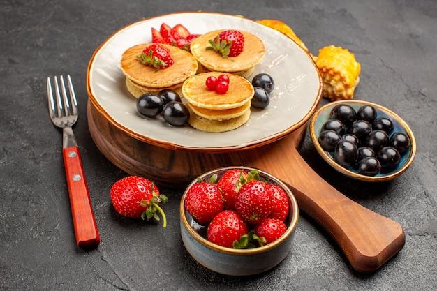 Vista frontal deliciosas panquecas com frutas na superfície escura bolo torta doce de frutas
