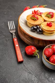 Vista frontal deliciosas panquecas com frutas na superfície escura bolo torta frutas doces