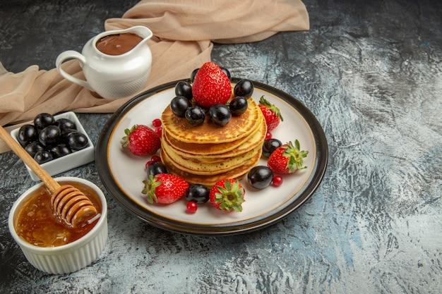 Vista frontal deliciosas panquecas com mel e frutas em um bolo de frutas doce de superfície clara