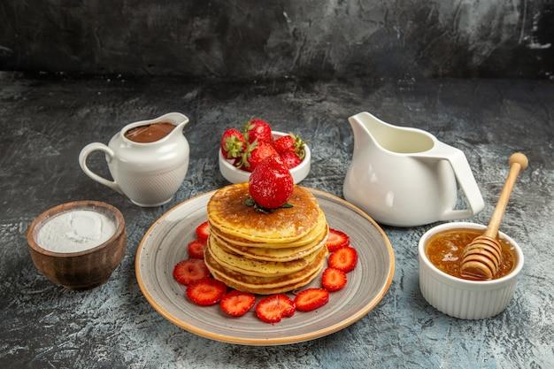 Vista frontal deliciosas panquecas com morangos e mel em bolo de frutas de superfície clara
