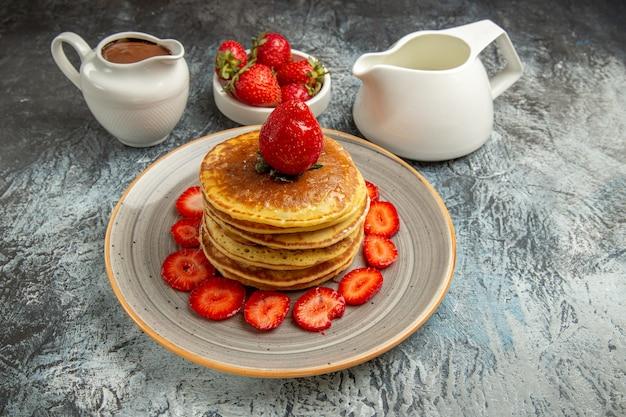 Vista frontal deliciosas panquecas com morangos e mel em um bolo de frutas doce de superfície clara