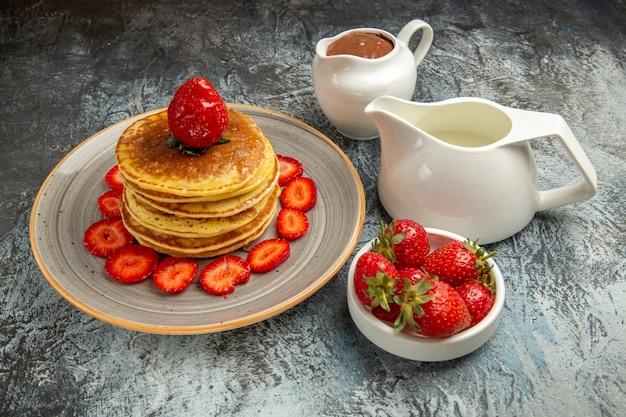 Vista frontal deliciosas panquecas com morangos e mel na superfície clara de bolo de frutas