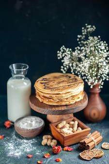 Vista frontal deliciosas panquecas com nozes na sobremesa de leite azul escuro doce torta bolo de manhã mel café da manhã
