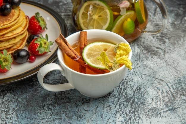 Vista frontal deliciosas panquecas com uma xícara de chá no bolo de frutas de chá de superfície clara