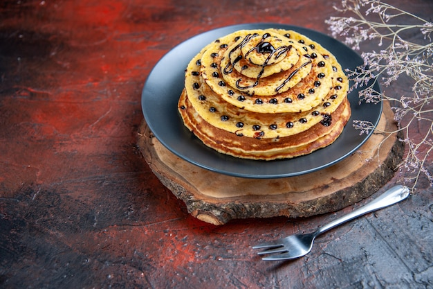 Vista frontal deliciosas panquecas doces com cobertura de chocolate em fundo escuro c