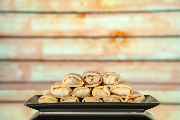 Vista frontal deliciosas panquecas enroladas dentro do prato com luz de fundo flor leite café da manhã bolo doce manhã açúcar sobremesa