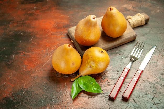 Vista frontal deliciosas peras doces em fundo escuro polpa maçã foto árvore frutífera