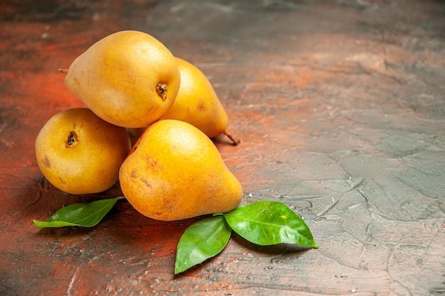 Vista frontal deliciosas peras doces em um fundo escuro de maçã com polpa de frutas