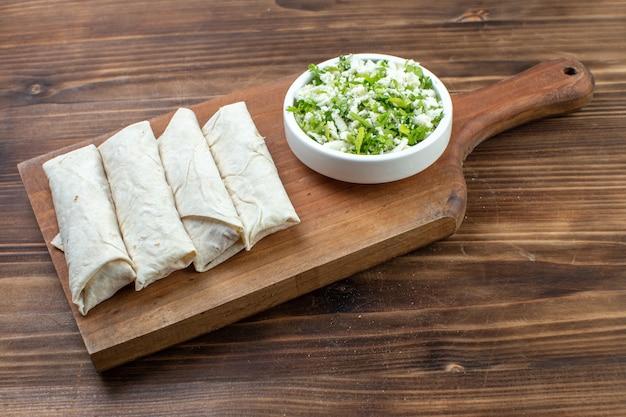 Vista frontal deliciosas pitas com verduras na tábua de corte fundo marrom farinha de massa cozinhar massa assar torta de azeite