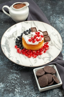 Vista frontal delicioso bolo cremoso com chocolate e passas em fundo claro-escuro biscoito doce sobremesa biscoito açúcar