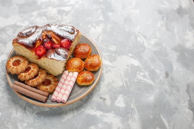 Vista frontal delicioso bolo de morango com biscoitos e bolinhos na superfície branca