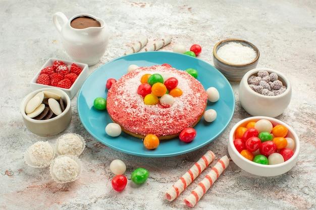 Vista frontal delicioso bolo rosa com doces coloridos no fundo branco cor do arco-íris bolo doce