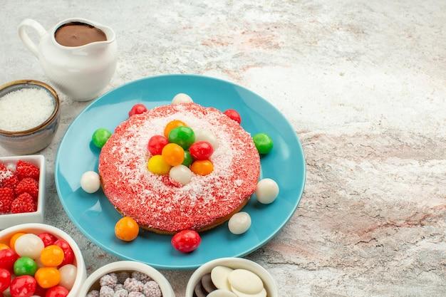Vista frontal delicioso bolo rosa com doces coloridos no fundo branco cor sobremesa bolo de doces arco-íris