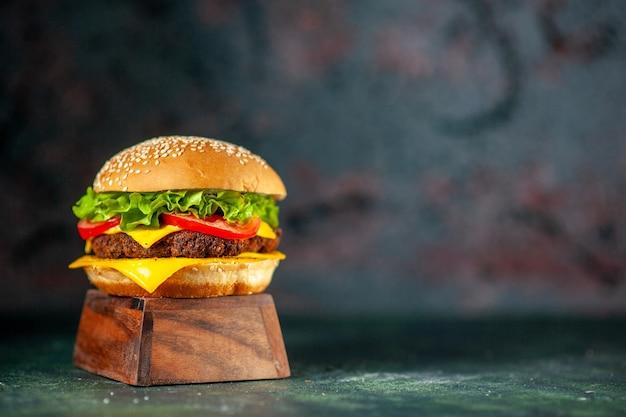 Vista frontal delicioso cheeseburger em fundo escuro