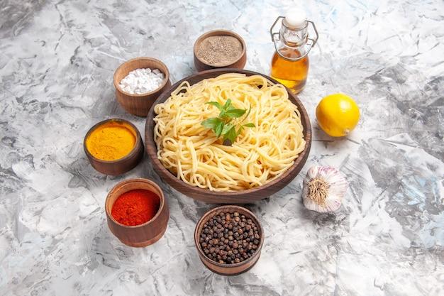Vista frontal delicioso espaguete com temperos na mesa branca refeição massa prato massa