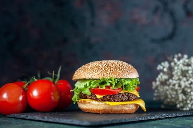 Vista frontal delicioso hambúrguer de carne com tomate vermelho em fundo escuro