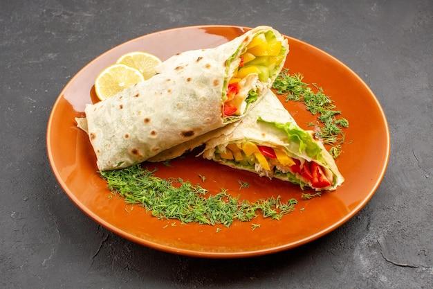 Vista frontal - delicioso sanduíche de salada shaurma fatiado dentro do prato no espaço escuro