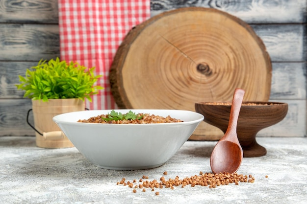 Vista frontal delicioso trigo mourisco cozido dentro do prato no espaço em branco