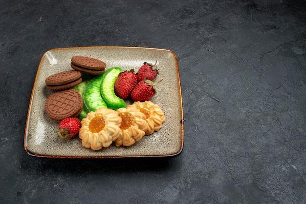 Vista frontal deliciosos biscoitos de chocolate e simples com morangos vermelhos frescos em bolo de biscoito de açúcar de parede cinza escuro