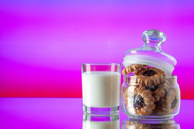 Vista frontal deliciosos biscoitos doces dentro de lata com copo de leite em um fundo rosa claro cor açúcar café da manhã bolo de manhã sobremesa refeição biscoito