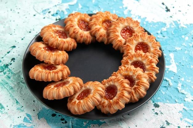 Vista frontal deliciosos biscoitos redondos formados com geleia dentro de uma placa preta na parede azul-clara.