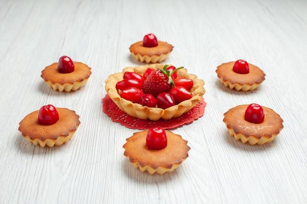 Vista frontal deliciosos bolinhos com frutas na mesa branca bolo biscoito sobremesa doce