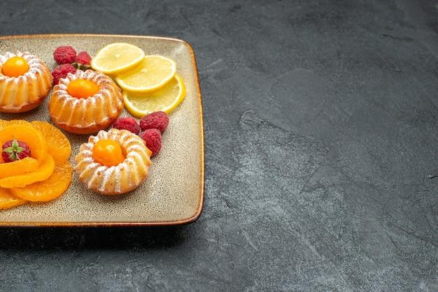 Vista frontal deliciosos bolinhos com rodelas de limão e tangerinas no espaço escuro